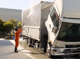 トラックを洗車する作業員