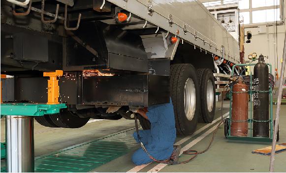 トラックの下に屈む作業員